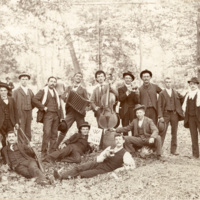 Men with musical instruments drinking in woods