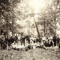 Large group with musical instruments drinking in woods